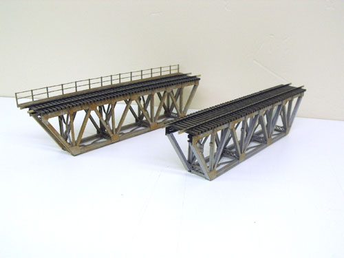 A pair of assembled Atlas HO Code 83 Warren Truss bridges, one with scratch built handrails.